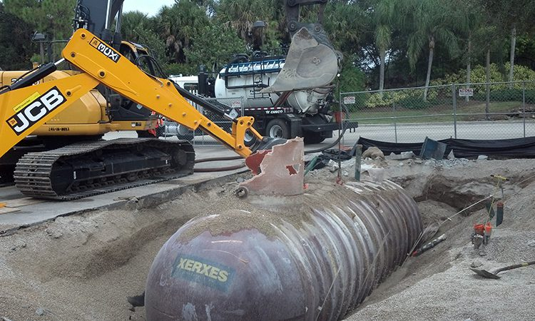 Excavator digging up a buried tank for removal
